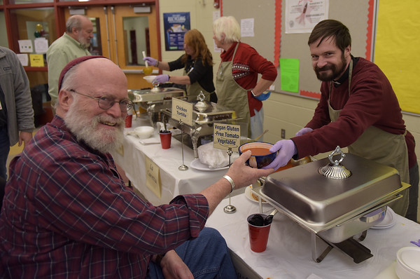 TIM JEAN/Staff photo <br /> <br /> Peter Levy, left, Rabbi Etz Hayim Synagogue in Derry, receives a bowl of soup from Zac Harmon, Vicar of St. Christopher's Episcopal Church in Hampstead, during the 15th annual Potter's Bowl fundraiser to benefit Community Caregivers of Greater Derry. The event was held at Pinkerton Academy in Derry, NH.     2/1/20