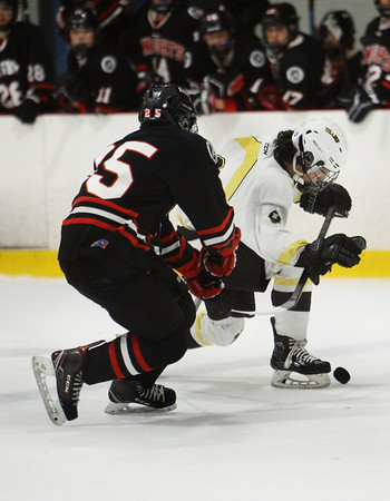 CARL RUSSO/Staff photo Haverhill's Evan Foskett, right, and North Andover's Nick Herald fight for the puck. North Andover defeated Haverhill 6-2 in boys' hockey action. 2/05/2020