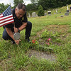 TIM JEAN/Staff photo<br /> <br /> Lawrence Police  Lt. Maurice Aguiler places a flag on veterans grave at the Bellevue Cemetery in Lawrence.       7/1/20