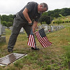 TIM JEAN/Staff photo<br /> <br /> Stephen Perrone, of Methuen, also a Army veteran places a flag on a veterans grave at the Immaculate Conception Cemetery in Lawrence. Dozens of volunteers helped out Lawrence Veterans Services by placing flags on graves.     7/1/20