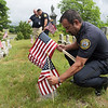 TIM JEAN/Staff photo<br /> <br /> Lawrence Police Chief Roy Vasque places a flag on veterans grave at the Bellevue Cemetery in Lawrence. Behind the chief are LT. Michael McCarthy and Lt. Maurice Aguiler. Dozens of volunteers helped out Lawrence Veterans Services by placing flags on graves.     7/1/20