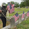 TIM JEAN/Staff photo<br /> <br /> Jackie Marmol of Lawrence a Army veteran replaces the old flags on veterans grave at the Bellevue Cemetery in Lawrence. Dozens of volunteers helped out Lawrence Veterans Services by placing flags on graves.     7/1/20