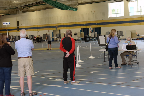 TIM JEAN/Staff photo<br /> <br /> Andover residents wait in line to pick up their ballots before voting in the Richard J. Collins Field House at Andover High during the state primary.  9/1/20