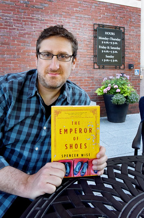 "BRYAN EATON/Staff photo. Spencer Wise has published his first novel, ""The Emperor of Shoes,"" about a father and son from the North Shore/Merrimack Valley working in the shoe business in China. Wise grew up in Andover, and mentions the town library in his acknowledgements."