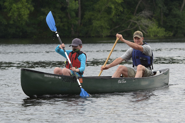 TIM JEAN/Staff photo<br /> <br /> Mike Pfendler, right, of Andover, and his son Peter, 9, make their way up river during a paddling and trash removal event on the banks of the Merrimack River. Paddlers made their way up river to start and floated back towards the collection area back at the boathouse. The event was organized by the Merrimack River Watershed Council and the Greater Lawrence Community Boating Program that offered participants a chance to clean up while on the Merrimack River around the Abe Bashara Boathouse in Lawrence.   7/17/21