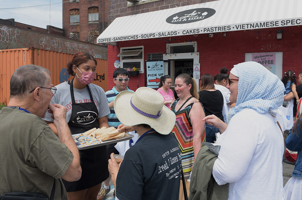 TIM JEAN/Staff photo<br /> <br /> In center, Joselyn Portorreal, of Lu's Cafe and Bakery offers samples of baked goods on the restaurant tour during Imagina Gastronomia, the second in the Imagina Essex series in downtown Lawrence. The event featured a pop up farmers market style food businesses, cooking demonstrations and even a restaurant walking tour.    7/17/21