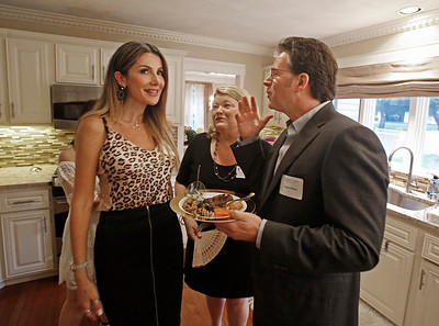 MIKE SPRINGER/Staff photo Karine Nabbout, left, visits with novelist Andre Dubus III, right, and his sister Suzanne Dubus, CEO of the Jeanne Geiger Crisis Center, during an event Thursday for the Geiger Center at the Andover home of Nabbout and her husband, Elias Nabbout. 6/20/2019