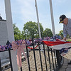 TIM JEAN/Staff photo<br /> <br /> Russell Chaput, 89, of Haverhill, adjusts one of the patriotic displays on the Korean War Veterans Memorial in GAR Park, Haverhill. The local Korean War Veterans, not the city, pay for all the maintenance and upkeep of the memorial.     6/2/21
