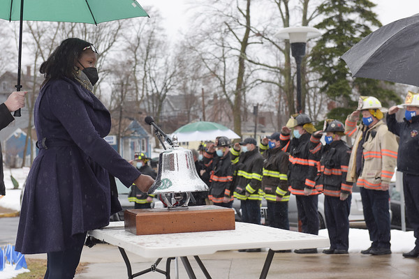 TIM JEAN/Staff photo<br /> <br /> Methuen City Councilor Eunice Zeigler rings the bell during a Covid-19 victims memorial ceremony outside the Quinn Public Safety Building. The event included the Methuen Police Honor Guard, Methuen Fire Department a moment of silence, and a symbolic 71 bell tolls to represent the lives lost.  3/1/21