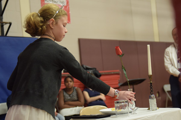 TIM JEAN/Staff photo<br /> <br /> Fourth grader Amelia Wieczorek places a rose in a vase with a red ribbon for the hope that all our missing will return some day at the conclusion of America's White Table, during a Salute to Veterans program at the Pvt. Albert E. Thomson Elementary School. The school is named in honor of Pvt. Albert E. Thomson, who was killed in World War I on Nov. 9, 1918, 100 years ago this day.  11/9/18