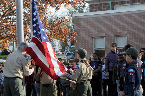 TIM JEAN/Staff photo<br /> <br /> Scoutmaster Jeff Keeton leads Boys and Cub Scout Troop 82 attach the flag to be raised at the start of a Salute to Veterans program at the Pvt. Albert E. Thomson Elementary School. The school is named in honor of Pvt. Albert E. Thomson, who was killed in World War I on Nov. 9, 1918, 100 years ago this day.  11/9/18