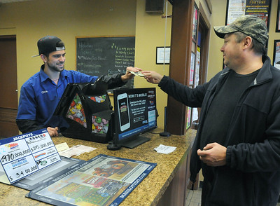CARL RUSSO/Staff photo. Chris Touma sells Shawn Deschene of Derry Mega Millions tickets. People from all over line up at Ted's State Line Mobil in Methuen to buy Mega Millions tickets because of the large jackpot. 10/18/2018