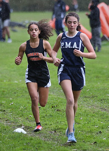 MIKE SPRINGER/Staff photo Elaina Latino, right, of Presentation of Mary Academy runs to victory ahead of second place finisher Nixvelisse Andino of Greater Lawrence Technical School in a varsity cross country meet Wednesday at Lawrence. 10/16/2018