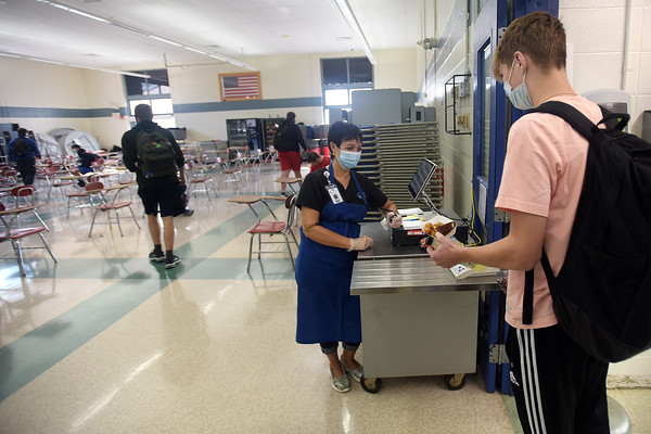 Cafeteria worker Teresa Cardoso, left, checks out a student in the lunchroom at Londonderry High School. Londonderry is getting creative and making more than ever from scratch, simply out of necessity because of the supply issues across the region.  10/12/21