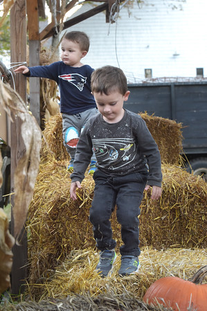 William Hewson, 4, front, and his brother Benjamin, 2, play on the hay bales at Boston Hill Farm in North Andover. The farm features pick your own apples, pumpkins, as well as fall treats such as apple cider donuts and a full bakery, and even has an ice cream parlor.  10/12/21