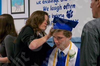 Zachary Coughlan gets some help from his mom, Cynthia Coughlan, with securing his graduation cap in place before the ceremony.