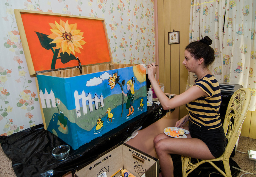 . Zoe Cohen paints a toy box to match the 1970\'s decor that fills the Fitchburg home of Independent filmmaker Jenn Potts as she prepares to shoot her short film \'The Extraordinary World Of Cecily Blinkstop\', as seen on Wednesday, July 12, 2017. SENTINEL & ENTERPRISE / Ashley Green