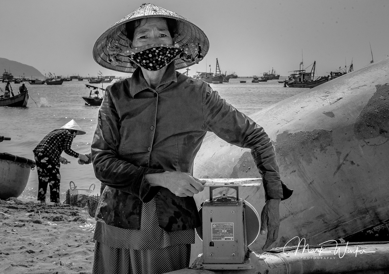 Woman with Scale for Weighing Fish in a fishing village outside of Phan Thiet