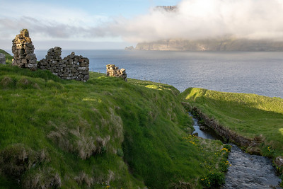 Exploring further one finds old stone buildings decaying along the grass covered shore line.  Almost always with a dramatic view of the next island of peninsula over and low hanging clouds.  This is Trollanes on the far north of Kalsoy