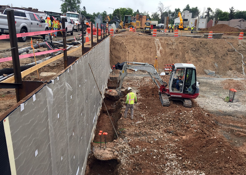 An excavator digs Wednesday, July 12, 2017, along the form for the north wall of the underground parking garage that will extend under the Cleveland Avenue apartment/retail building at The Foundry redevelopment project in downtown Loveland. (Photo by Craig Young / Loveland Reporter-Herald)