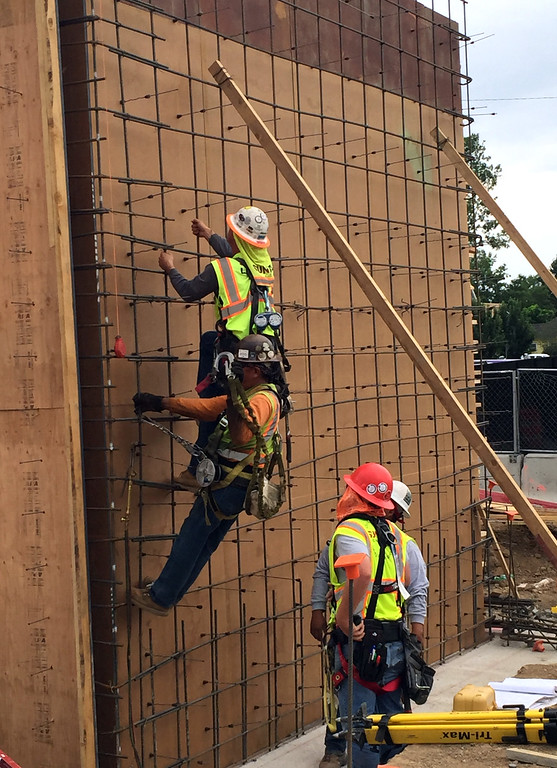 . Workers climb up the form for the elevator shaft at the northeast end of the Lincoln Avenue apartment/retail building at The Foundry redevelopment project in downtown Loveland on Wednesday, July 12, 2017. (Photo by Craig Young / Loveland Reporter-Herald)