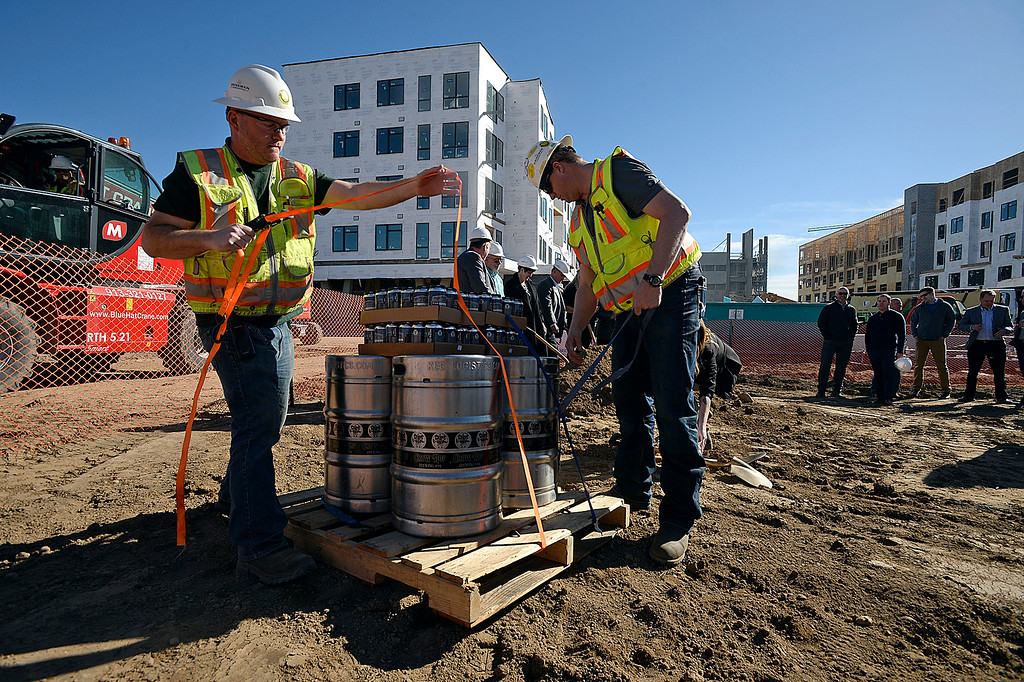 ". Brinkman Construction employees Ben Bradley, left, and Josh Bob remove saftely straps from cases and kegs of The Foundry Cream Ale after it was delivered by a huge forklift Wednesday, March 7, 2018, while celebrating the ""topping out\"" of The Foundry\'s two mixed-use/apartment buildings and the parking garage, and the groundbreaking for the hotel and the movie theater. The beer was created by a collaboration with Brinkman employees and Crow Hop Brewing which is right in the heart of the construction area. (Photo by Jenny Sparks/Loveland Reporter-Herald)"