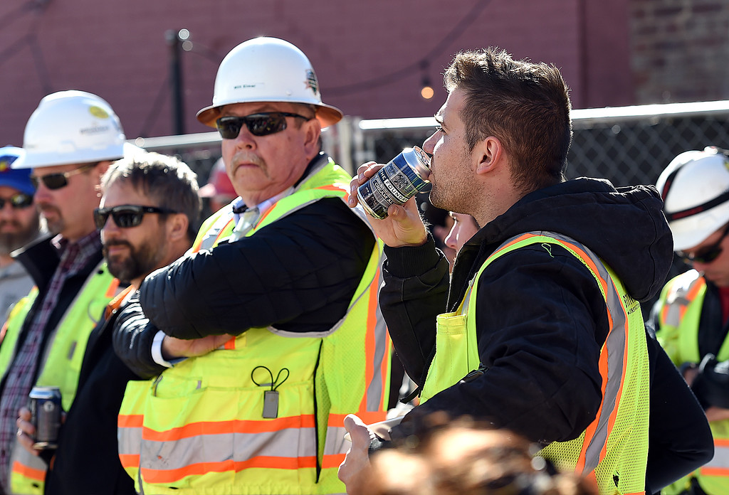 ". Attila Riczak, right, a construction worker with Brinkman Construction, gets a taste of The Foundry Cream Ale Wednesday, March 7, 2018, while celebrating the ""topping out\"" of The Foundry\'s two mixed-use/apartment buildings and the parking garage, and the groundbreaking for the hotel and the movie theater. The beer was created by a collaboration with Brinkman employees and Crow Hop Brewing which is right in the heart of the construction area. (Photo by Jenny Sparks/Loveland Reporter-Herald)"
