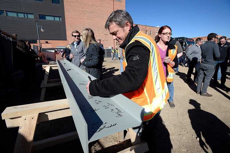 "Patrick Eastman with Neuworks Mechanical signs a steel beam Wednesday, March 7, 2018, while celebrating the ""topping out"" of The Foundry's two mixed-use/apartment buildings and the parking garage, and the groundbreaking for the hotel and the movie theater.  (Photo by Jenny Sparks/Loveland Reporter-Herald)"