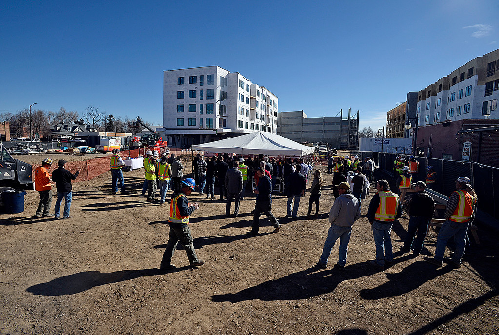 ". Construction crews, officials and other people gather Wednesday, March 7, 2018, for a celebration of the ""topping out\"" of The Foundry\'s two mixed-use/apartment buildings and the parking garage, and the groundbreaking for the hotel and the movie theater.  (Photo by Jenny Sparks/Loveland Reporter-Herald)"