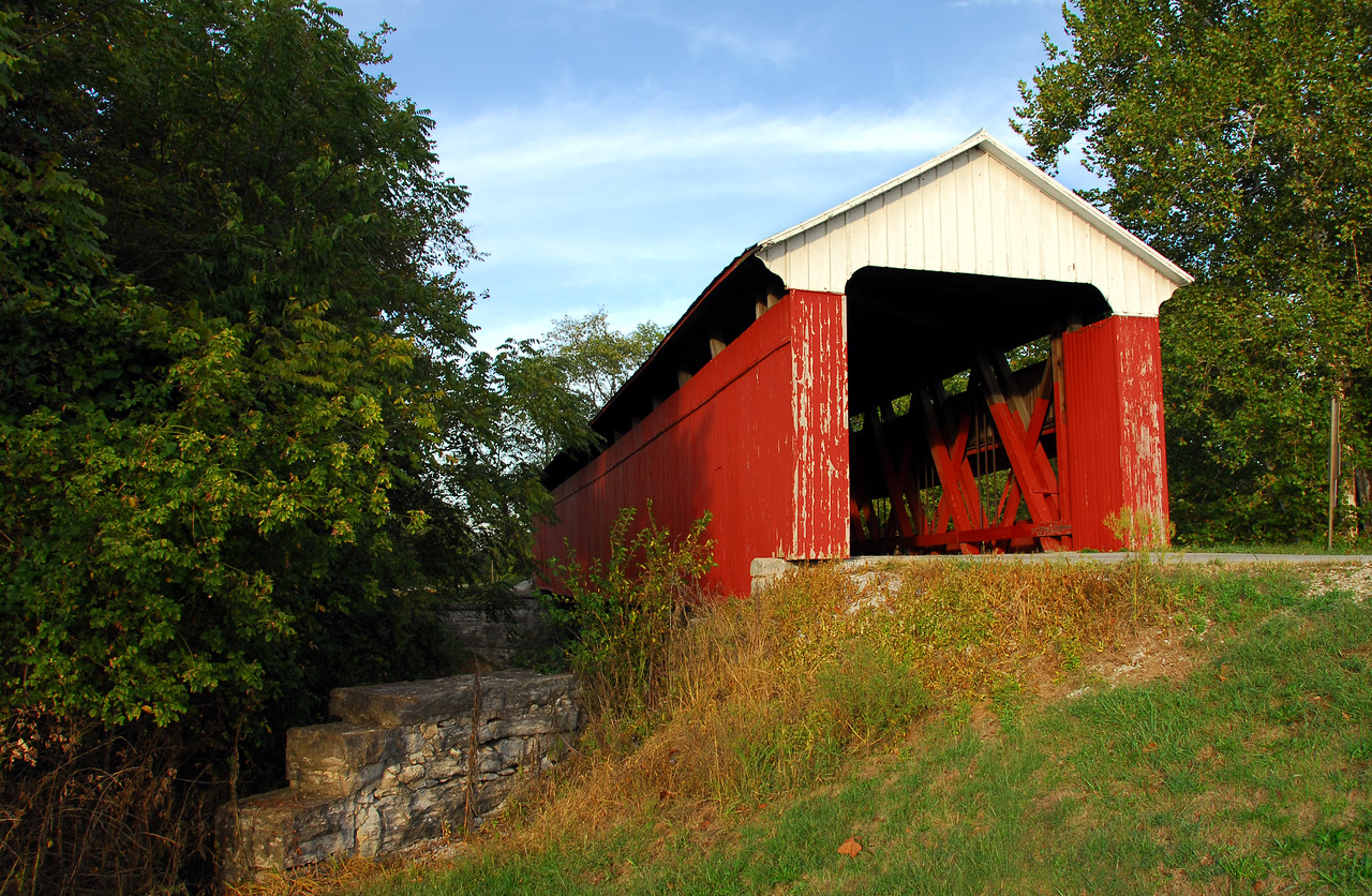 "This covered bridge is located in Scipio, Indiana. It is a rickety old bridge but still sturdy enough to be functional today. As you cross over the wooden floor, you can hear the sound of the wooden planks shifting under the load of the vehicle. The charm of the bridge ""outweighs"" any fears one may have in testing its sturdiness for traffic, foot, horseless or horsedrawn. One can be transported back in time by listening to the sounds that surround the ol' reliable. Each time a car approaches, it honks a warning to walkers or vehicles approaching from the opposite direction. This photograph has been desaturated and sepia tinted. The sepia photograph is also displayed in this gallery."