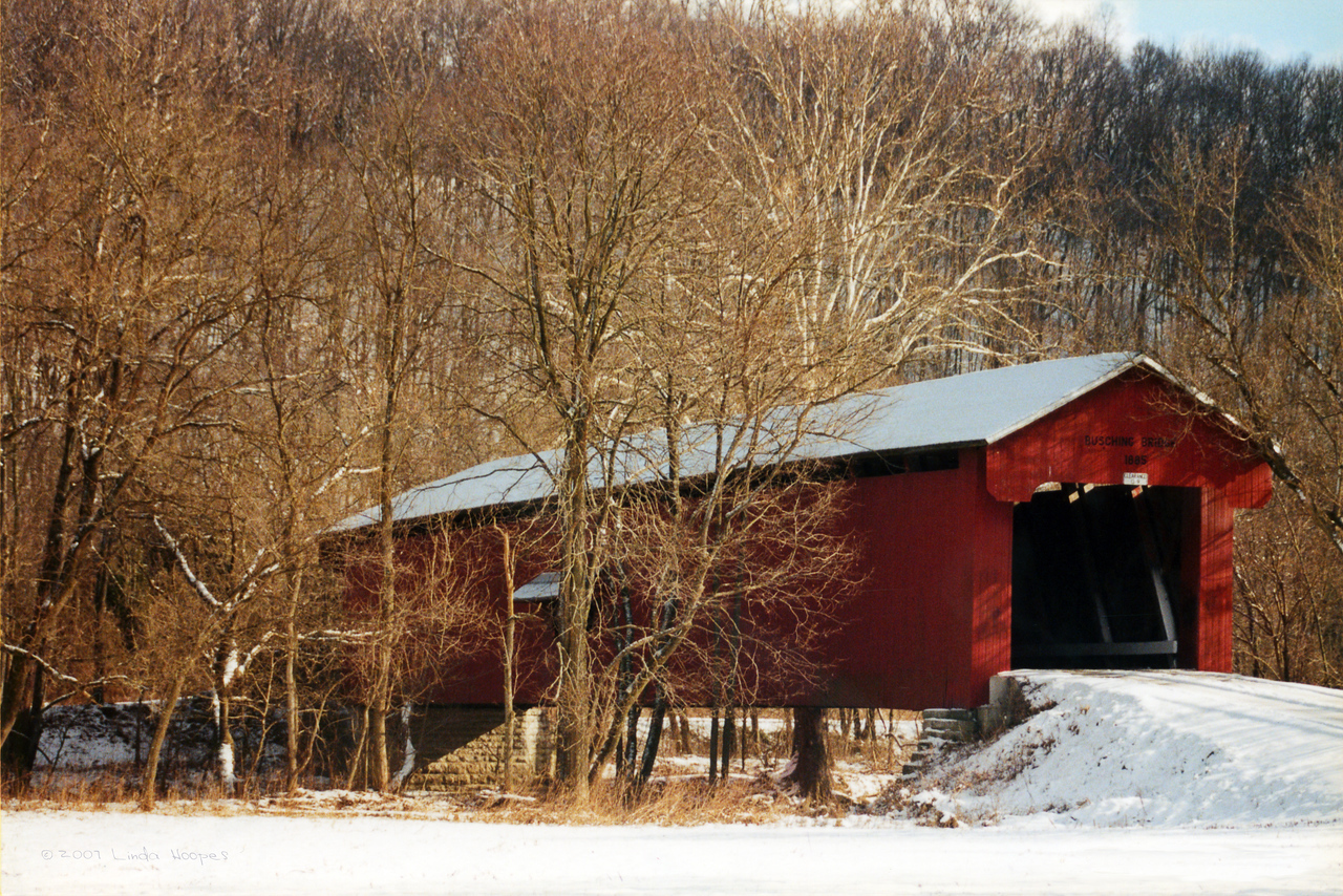 Busching Bridge surrounded in a blanket of snow. This covered bridge is still in use today. It can be found just outside the entrance to Versailles State Park, Versailles, Indiana