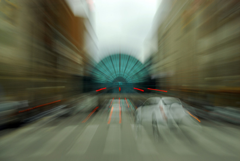 This is a photograph taken in Downtown Indianapolis. Traveling towards Indianapolis Art Gardens I zoomed into the art gardens building.The vehicle on the right adds to the feeling of motion in the picture.