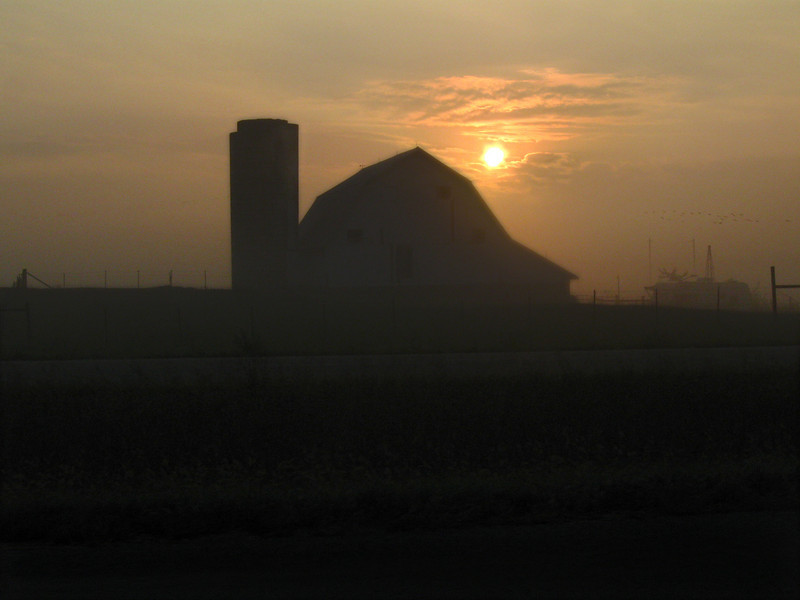 The silhouette of a barn and silo appear in the foreground of the first morning light