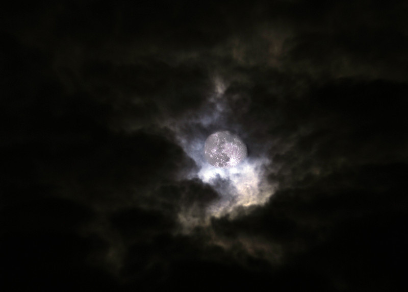To get this photograph, two photographs were combined as layers in Photoshop because exposing to bring out the detail of the clouds blew out the detail in the moon. With two photographs at different exposure times, a shorter time for the moon and about twice as long for the clouds and then combining them, this photograph was created. The clouds photo was made when the moon was almost completely blocked by the thick clouds.