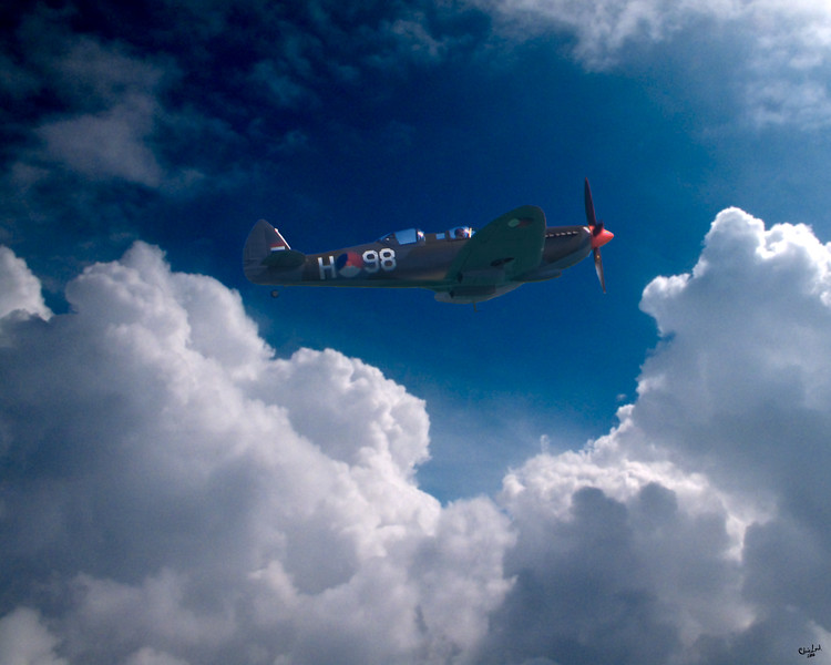 A Spitfire with Unusual Rear Cockpit Flies Through a Clearing in the Clouds