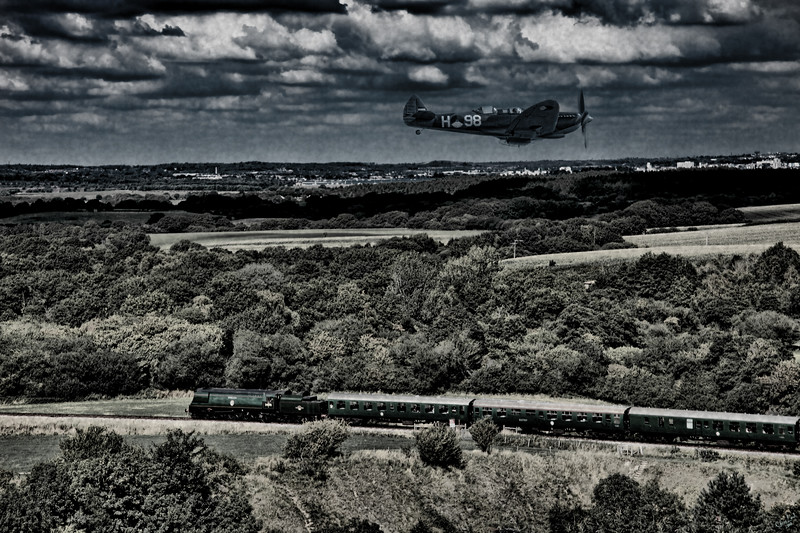 A Spitfire with Dutch Insignia Flies over a Steam Train