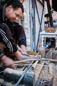 A craftsman at the ancient Marrakech medina making chess pieces out of cedar, using this hand-powered lathe.