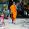 A Monk walks through the Tep Preah nom Pagoda while a girl and a dog play in the humid mid morning Cambodian air. <br /> <br /> Canon 5D Mark III, Canon 28-300, 1/500 sec, f/5.6