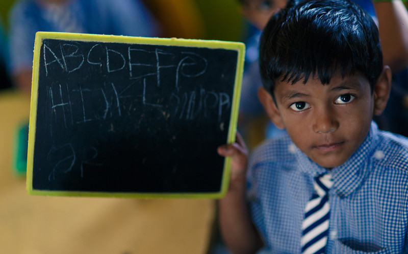 A boy shows he can write his ABC's at a school in India.   Canon 5D Mark III, Sigma 85mm, 1/500 sec, f/1.4