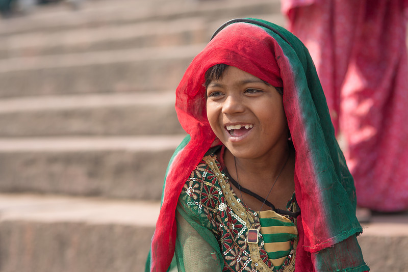 A girl laughs on the steps of a mosque in Old Delhi, India.  Canon 5D Mark III, Sigma 85mm, 1/1000 sec, f/2.8