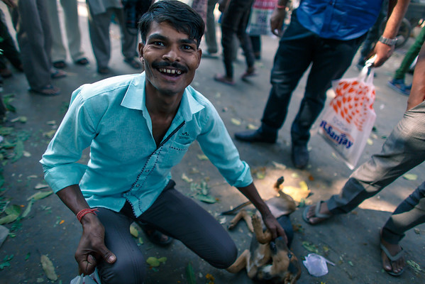 Dog Day Afternoon - New Delhi, India  A man plays with a pooch in a street market in New Delhi. Taken on the recent workshop I co-led for +The Giving Lens. Want to join one of these incredible journeys? Sign up today!  http://thegivinglens.com/workshops/  #TGLIndia #Photography #India #Portrait #Street