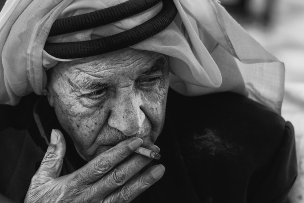 An old man enjoys a cigerette while he plays a local board game in the central square in Al-Salt, Jordan