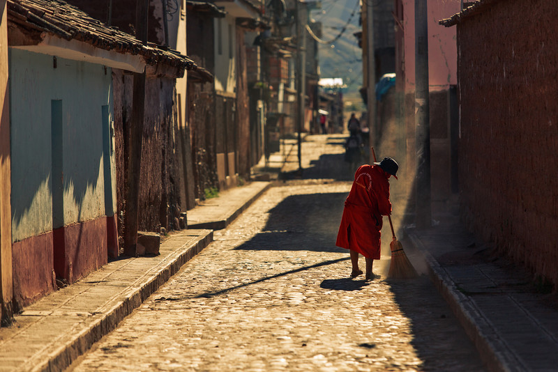 A woman sweeps the streets of Oropesa Peru in the afternoon light.
