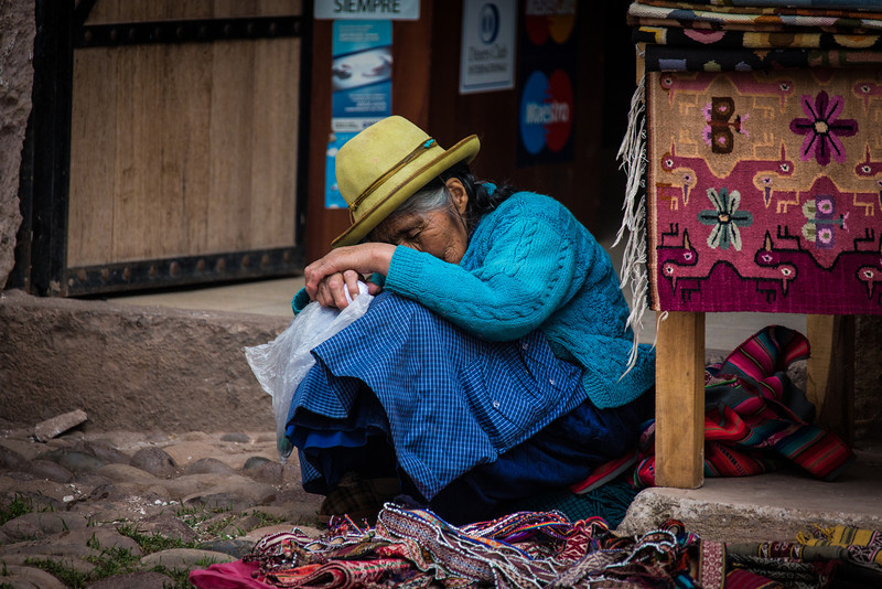An old merchant woman takes a nap at her stall in Peru.