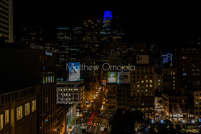 Night Scene San Francisco California skyline. Salesforce tower with blue glow and moon on top. Post Street with car lights trails and stores. Union Square right foreground. Editorial photo.