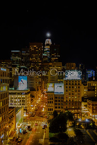 Night Scene SAn Francisco California skyline. Salesforce tower with moon on top. Post Street with car light trails leading to base of salesforce tower. Union square on the right foreground.