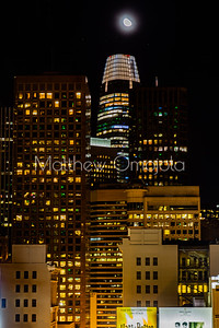 Night Scene San Francisco California skyline. Salesforce tower top with white glow and moon on top.