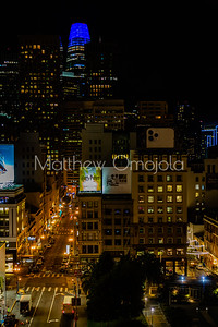 Night Scene San Francisco California skyline. Salesforce tower with moon on top. Post Street with stores. Union Square right foreground.