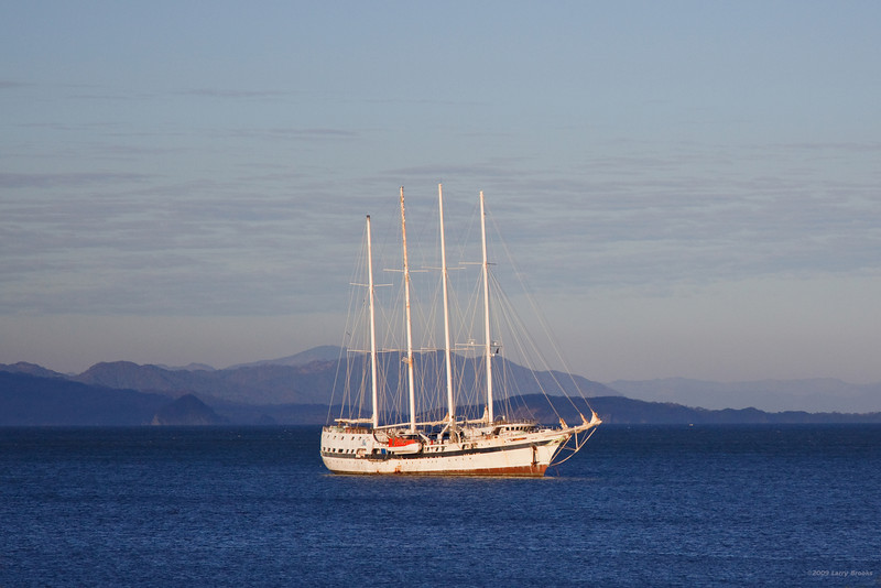 The bay near Jaco makes a scenic backdrop for an anchored sailboat