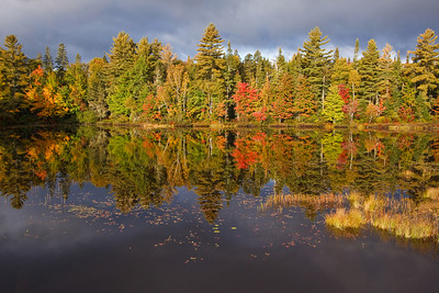 A clearing storm adds dramatic effect to Autumn reflections on a pond alongside the Androscoggin River.